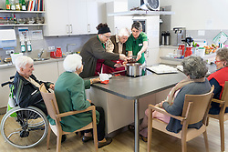 Nurses preparing food with senior inhabitants in rest home