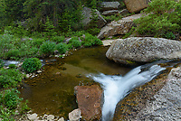 A small cascade on Beaver Creek flows through a verdant valley in the northern Bighorn Mountains.