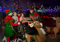 Kaleigh Booth and Payten Blais take a ride in Santa's sleigh to the North Pole with Elfis and Jack Frost during opening night of Christmas Village Thursday evening.  (Karen Bobotas/for the Laconia Daily Sun)