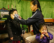 Dressing up her kids with air pollution masks before going out. The Otgonbaatar family live in a Ger District particularly affected by air pollution.<br /> Mongolia