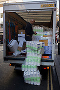 A man checks the delivery of toilet rolls from the back of a van in Soho, central London