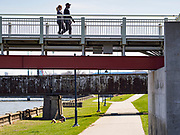 "01 APRIL 2020 - DES MOINES, IOWA: On People cross a bridge over the Des Moines River on a warm spring day in downtown Des Moines. Despite the pleasant weather, many people stayed indoors because the coronavirus (SARS-CoV-2) pandemic. On Saturday morning, 04 April, Iowa reported 786 confirmed cases of the Novel Coronavirus (SARS-CoV-2) and COVID-19. There have been 14 deaths attributed to COVID-19 in Iowa. Restaurants, bars, movie theaters, places that draw crowds are closed until 30 April. The Governor has not ordered ""shelter in place"" but several Mayors, including the Mayor of Des Moines, have asked residents to stay in their homes for all but the essential needs. People are being encouraged to practice ""social distancing"" and many businesses are requiring or encouraging employees to telecommute.    PHOTO BY JACK KURTZ"