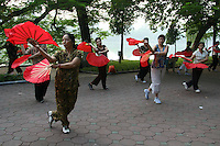Early morning along the shores of Hoan Kiem Lake fan dancing is popular with Vietnamese ladies.  Hoan Kiem Lake is right in the historical center of the city and one of the scenic spots of the city  serving as a focal point for its public life.