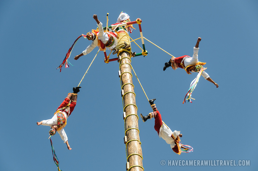 Four performers swing from ropes from a tall pole, recreating a traditional Mayan ceremony at Xcarat Maya theme park south of Cancun and Playa del Carmen on Mexico's Yucatana Peninsula.