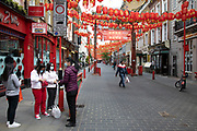 Group of women wearing face masks on Gerrard Street in Chinatown, which is eerily quiet and silent on empty streets as lockdown continues and people observe the stay at home message in the capital on 12th May 2020 in London, England, United Kingdom. Coronavirus or Covid-19 is a new respiratory illness that has not previously been seen in humans. While much or Europe has been placed into lockdown, the UK government has now announced a slight relaxation of the stringent rules as part of their long term strategy, and in particular social distancing.