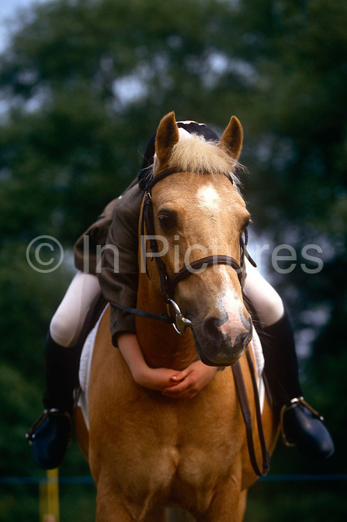 "A young girl hugs her beloved pony at a gymkhana meeting in Cheltenham, Gloucestershire, England. Gymkhana is an Indian Raj term which originally referred to a place where sporting events took place and referred to any of various meets at which contests were held to test the skill of the competitors. In the United Kingdom and east coast of the United States, the term gymkhana now almost always refers to an equestrian event for riders on horses, often with the emphasis on children's participation (such as those organised here by the Pony Club). Gymkhana classes include timed speed events such as barrel racing, keyhole, keg race (also known as ""down and back""), flag race, and pole bending."