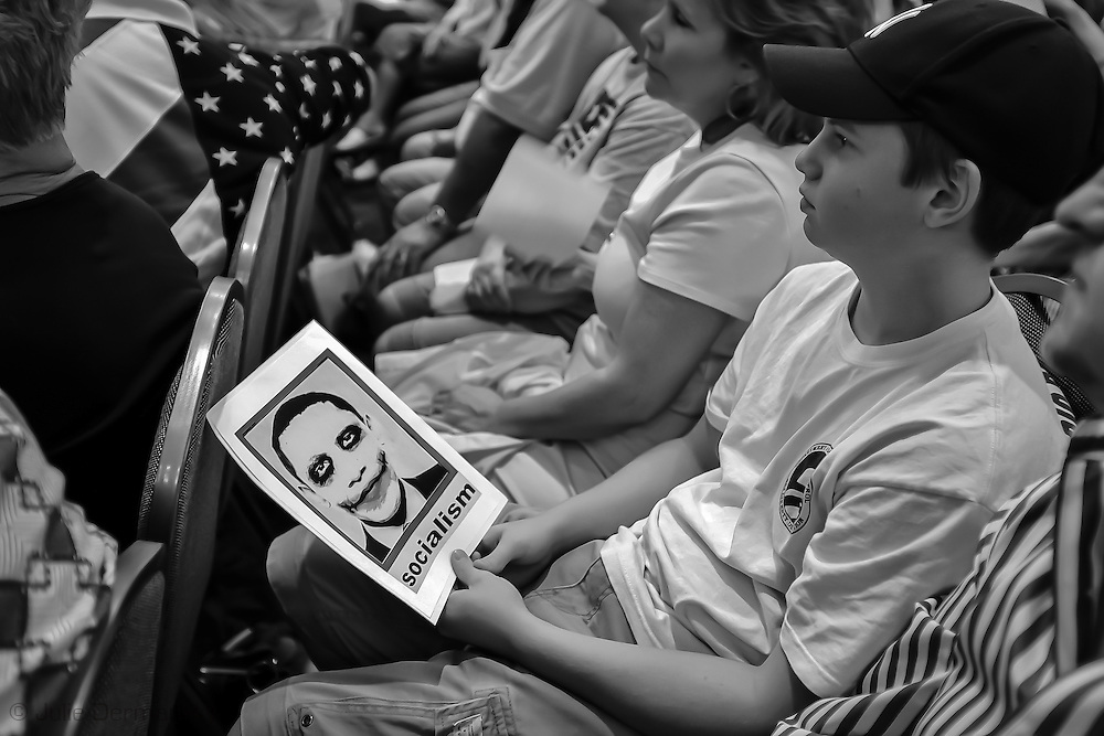 Crowd at a at a Tea Party  anti-Obamacare rally in Covington Louisiana. Young boy holds a racist anti President Obama flier.