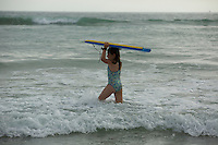 A 9 year-old girl with a biggie board in the ocean.