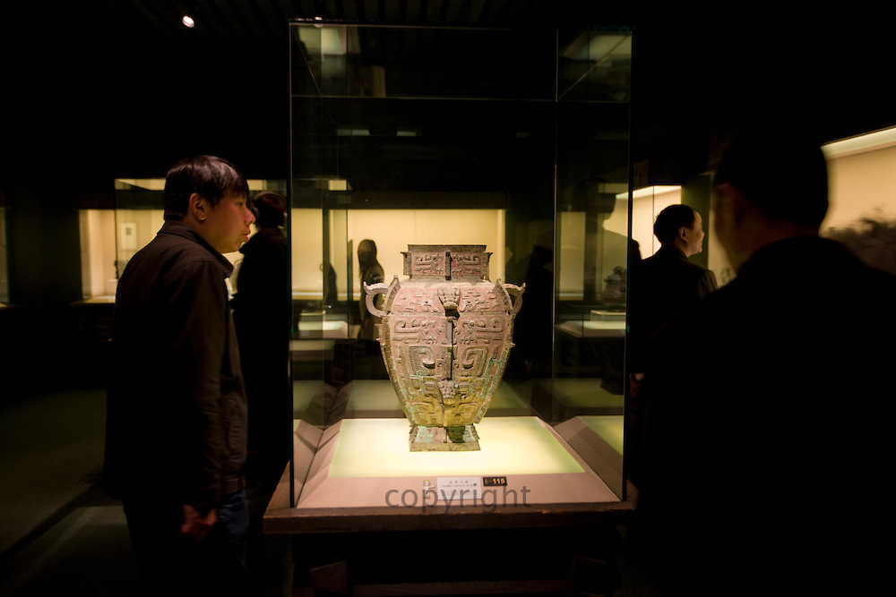 Visitors look at a water vessel on display in glass case in the Shanghai Museum, China