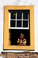 painted women at a window of the unesco world heritage city of ouro preto in minas gerais brazil