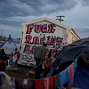 "A graffiti stating ""Fuck Racist Borders"" is seen on a wall of a container among thousands of tents set up by migrants at the Greek-Macedonian border station of Idomeni, Greece. Around 13,000 migrants and refugees, mostly from the Middle East and African nations, are believe to be stranded here awaiting a chance to proceed their journey towards Germany and other northern European countries."