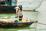 04 APRIL 2012 - HA LONG, VIETNAM:   A Vietnamese woman paddles a tender through the cruise ship harbor in Ha Long Harbor near Ha Long Bay. In 1994 UNESCO declared 174 square miles of Ha Long Bay a World Heritage Site. There are nearly 2000 distinct rock islands in the bay, which for centuries has been the home to isolated fishing villages. Now thousands of tourists stream through the bay and around the islands every day on cruise ships. On the Vietnamese mainland, around the town of Ha Long, real estate companies are developing exclusive condominium and apartment complexes for use as weekend homes for people in Hanoi, about a 3.5 hour drive from Ha Long.      PHOTO BY JACK KURTZ