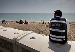 © Licensed to London News Pictures. 24/06/2021. Brighton, UK. A security guard watches over Brighton beach as visitors enjoy the warm sunny weather. After recent rain, a period of high temperatures and sunshine is forecast in the south. Photo credit: Peter Macdiarmid/LNP