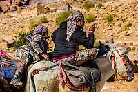 Bedouin man and boy on donkeys, Petra Archaeological Park (a UNESCO World Heritage Site), Petra, Jordan.