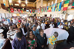 3 November 2019, Monrovia, Liberia: Congregants pray during Sunday service at the Providence Baptist Church, also known as 'the cornerstone of the nation', as it was in the Providence Baptist Church that Liberia's declaration of independence was signed. While this Sunday service is taking place in a larger worship space finalized in 1976, the old chapel remains in place adjacent to the new one, and is still in use.