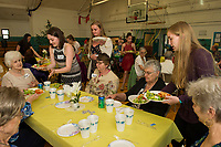 LHS seniors Katie DiBona, Lindsey Drouin and Danielle Friend serve the first course salad to Virginia, Peggy, Carol, Pat, Hannah and Cecile during the Senior Senior dinner and dance at the Laconia Community Center Thursday evening.  (Karen Bobotas/for the Laconia Daily Sun)
