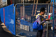 Young woman uses mobile phone amid Jubilee Line construction blue netting fences at Tottenham Court Road.