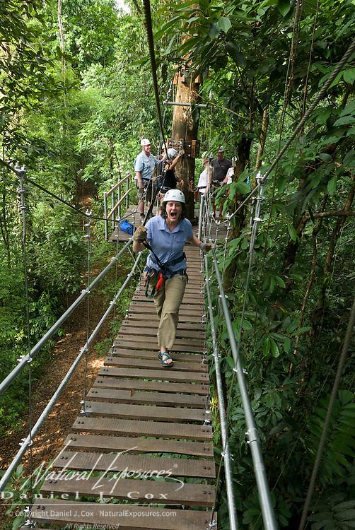 Tish crossing suspension bridge during zip line run. Costa Rica.