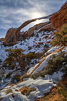 The sun shines through Landscape Arch on a warm Winter day in Arches National Park in Southern Utah.