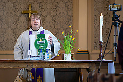© Licensed to London News Pictures. 22/03/2020. London, UK. Reverend Anne Bennett holds up a packet of toilet paper as she delivers the sermon during the Mothering Sunday service to parishioners via live-stream at the Church of the Ascension in Blackheath, south London. In response to government advice on social distancing and non-essential contact, the Church of England has suspended public worship until further notice to help slow the spread of the Coronavirus. Photo credit: Rob Pinney/LNP