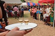 Mar. 14, 2009 -- LUANG PRABANG, LAOS: A hostess serves Johnie Walker Scotch to guests arriving at a wedding reception north of Luang Prabang, Laos.  Photo by Jack Kurtz / ZUMA Press