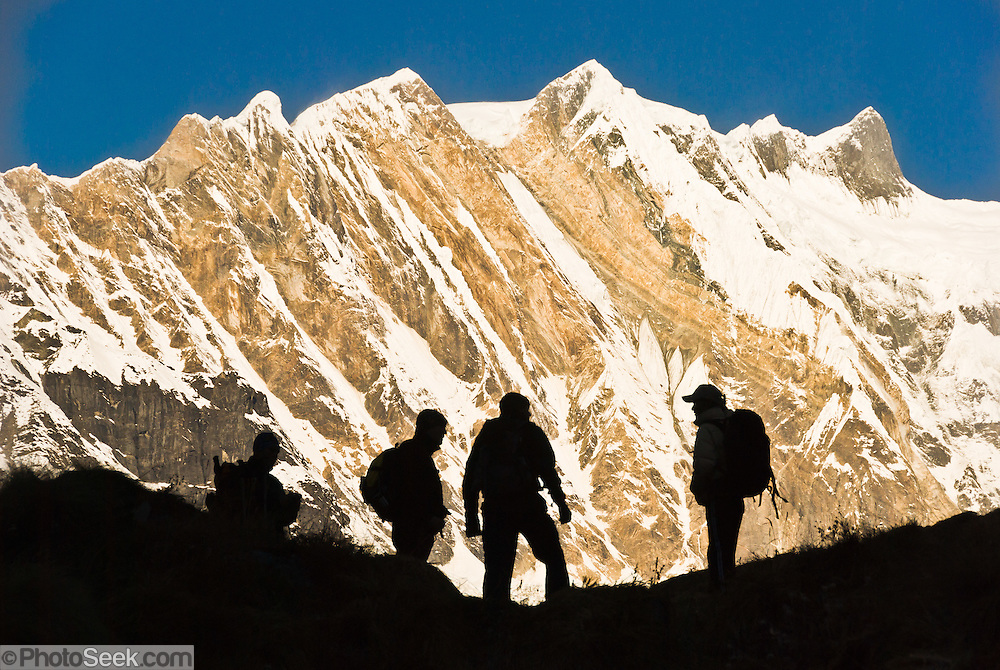 """The silhouettes of trekkers stand against the impressive mountain face of Fang (or Baraha Shikhar 25,088 feet / 7647 meters), in the Annapurna Range of Nepal. Published on the front cover of """"Light Travel: Photography on the Go"""" by Tom Dempsey 2009, 2010. Published September 29, 2016 in Amateur Photographer magazine, London, UK, """"Expert guide to silhouette photography"""": http://www.amateurphotographer.co.uk/technique/camera_skills/silhouette-photography-taking-shape-96009"""