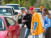 """11 MAY 2020 - DES MOINES, IOWA: Rev JEFF OSTRANDER (left center), JERRY CLUTTS, and GRACE OSTRANDER, Rev. Ostrander's daughter, put food into the back seat of a client's car at a """"no touch"""" emergency food pantry at DSM First Church in Des Moines. The emergency pantry at DSM First Church expanded from distribution one day a week to three days per week after the COVID-19 pandemic forced the closure of many Iowa businesses. Food banks and emergency pantries in Iowa continue to see increased demand for services, even though the governor is reopening the state's economy. Iowa's unemployment rate for April hasn't been released yet, but based on national trends, it is expected to soar to well over 10% from 3.8& in March. COVID-19 infections continue to skyrocket. On Monday, 11 May, the governor announced that 12,373 people tested positive for coronavirus (SAR-CoV-2) and  271 had died.               PHOTO BY JACK KURTZ"""