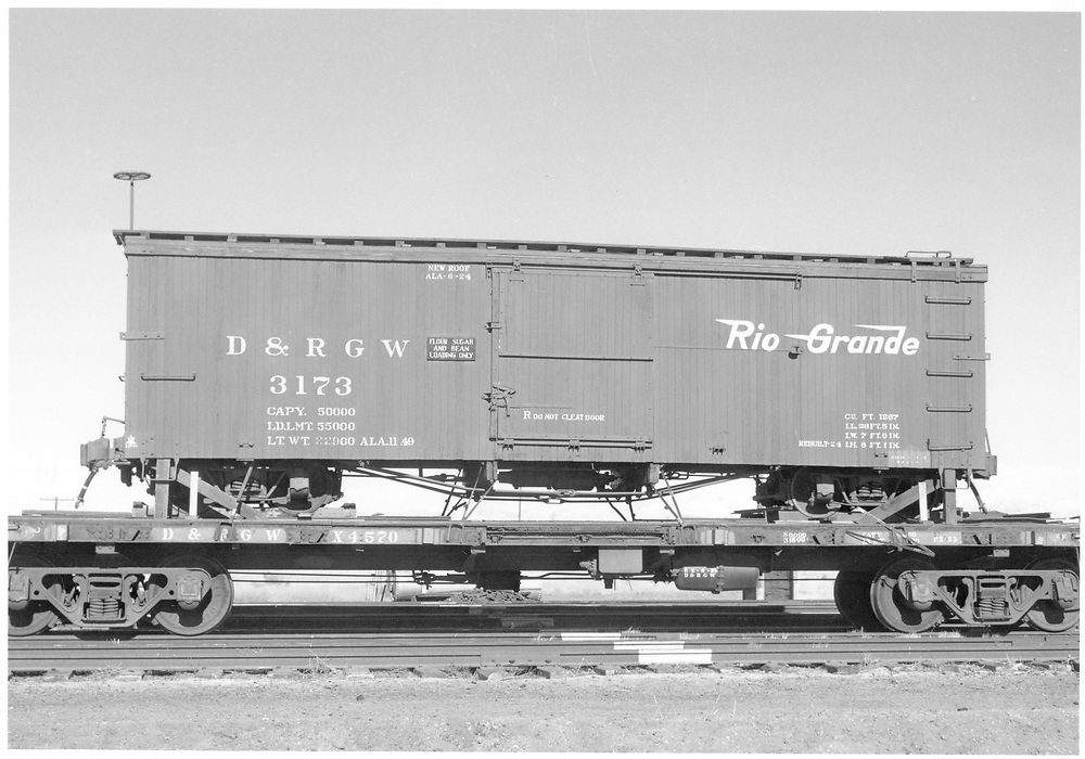 Side view of box car #3173 loaded on standard gauge flat car #X4570 at Alamosa.  This car was moved from Salida after cessation of narrow gauge operations there.<br /> D&RGW  Alamosa, CO  Taken by Richardson, Robert W. - 12/14/1955