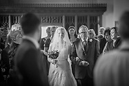 bride is walked down church aisle by her father on her wedding day