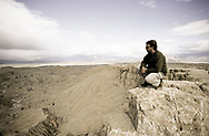 A man wearing sunglasses squats at the edge of a cliff overlooking the badlands of Anza Borrego Desert State Park in California.  Anza-Borrego Desert State Park is the largest state park in California. (releasecode: jk_mr1024) (Model Released)