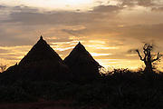 Africa, Ethiopia, Omo River Valley Hamer Tribe silhouette of huts at sunset