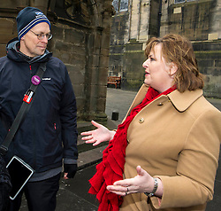 Pictured: Gary Mill, tour guide with Mercat Tours, provided some history for Fiona Hyslop used the Mercat Cross key to get a special view of the High Street.<br /> Ahead of parliamentary debate on the Year of History, Heritage and Archaeology, Culture Secretary Fiona Hyslop visited Edinburgh's Mercat Cross on the High Street to learn how Scotland is capitalising on the booming demand from tourists to explore the nation's history and genealogy. <br /> Ger Harley | EEm 31 January 2017