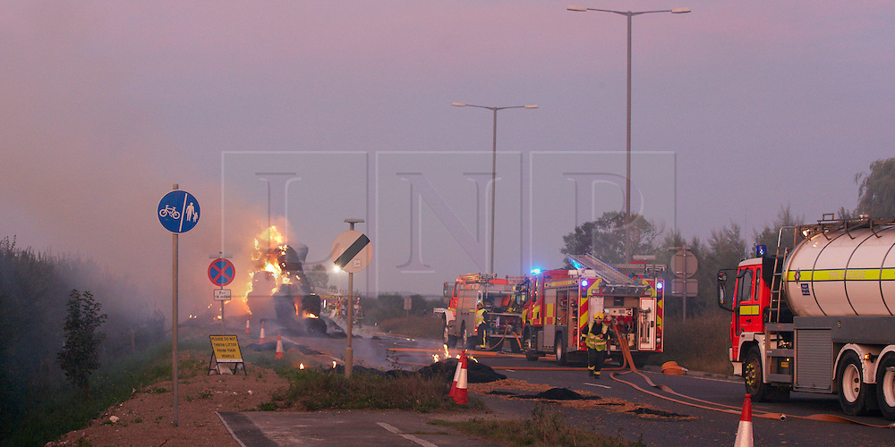 © Licensed to London News Pictures.  06/09/2012. AYLESBURY, UK. Fire fighters deal with a large hay lorry fire on the A41 near Aston Clinton. The driver Philip Judge (not pictured) attempted unsuccessfully to shed the burning hay leaving a trail some 200 metres long before abandoning his lorry and escaping uninjured. Photo credit :  Cliff Hide/LNP