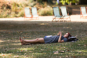 A woman with a book lying on the grass in St Jamess Park in London, England during the ongoing summer heatwave on August 07, 2018.