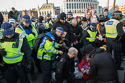 London, UK. 17th November, 2018. Police officers use cutting gear after environmental campaigners from Extinction Rebellion used lock-on tubes to block Blackfriars Bridge, one of five bridges blocked in central London, as part of a Rebellion Day event to highlight 'criminal inaction in the face of climate change catastrophe and ecological collapse' by the UK Government as part of a programme of civil disobedience during which scores of campaigners have been arrested.