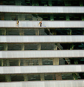 Two men cleaning the windows on the side of the Torre Mapfre building, and office block, in the Port Olympic in Barcelona, Spain