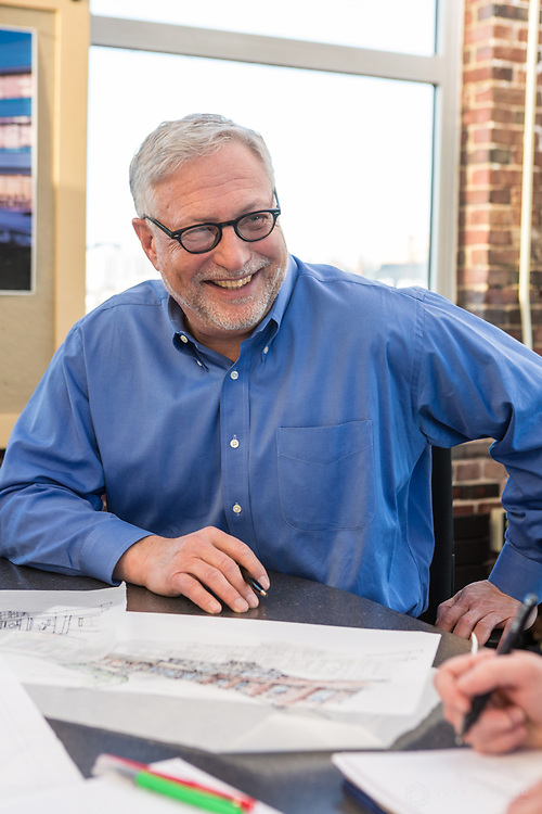 An architect smiles during a meeting.