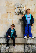 Two children (5 years old, 9 years old) beside stone gargoyle, Dubrovnik old town, Croatia