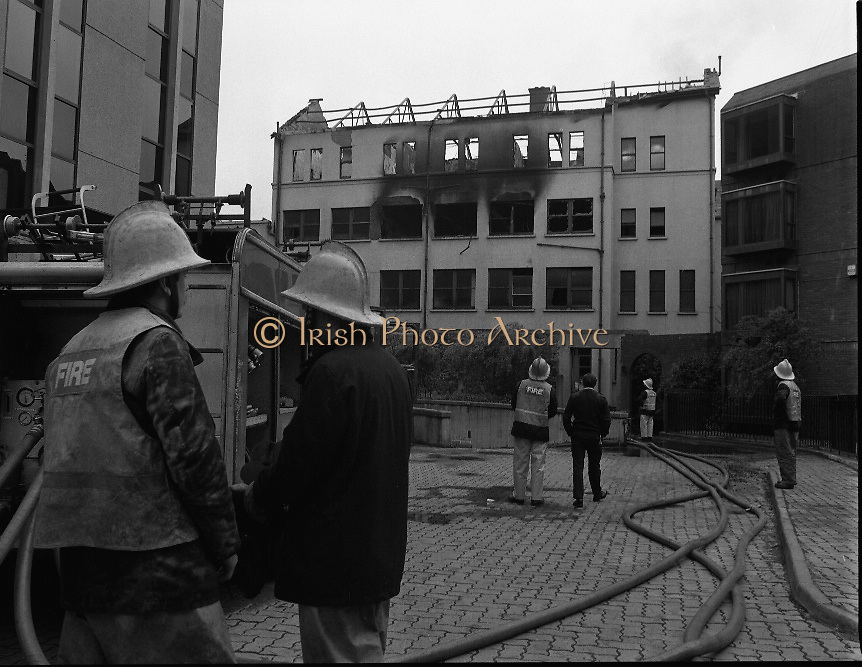 Fire at Loreto (On The Green)..1986..02.06.1986..06.02.1986..2nd June 1986..The aftermath of the disasterous fire at Loreto Convent which claimed the lives of six elderly nuns. The nuns were retired teachers at Loreto College for Girls which is attached to the convent. The nuns were named as Sisters' Edith,Eucharia,Seraphia,Margaret,.Rosario and Gonzaga. Fifteen other nuns managed to escape the inferno. The convent was said to be over 150 years old,the nuns resided in dorms on the top floor. Fire authorities were today trying to determine the cause of the fire...Picture shows Dublin Fire Brigade crews looking at the scene of the blaze which they had now extinguished. The outbreak of fire was on the top floor of the convent in the nuns dormitories. The nuns who died were said to be aged between sixty and eighty years of age.