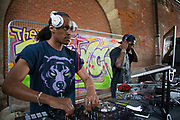 Young people gather for an urban street culture weekend on the Southbank. Here underneath Hungerford Bridge, DJ3D lays down the music on his laptop and decks. The South Bank is a significant arts and entertainment district, and home to an endless list of activities for visitors and tourists alike.