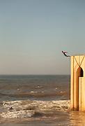 Man jumping off high wall into rough sea near Corniche on bright sunny day, Casablanca, Morocco