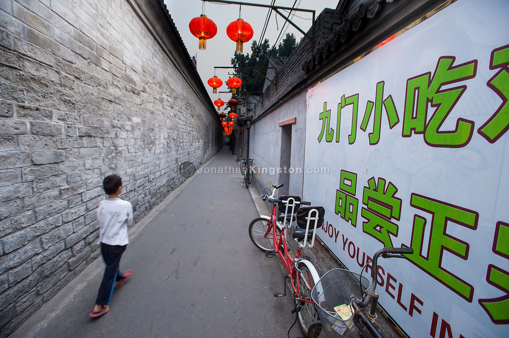A young boy walking down the narrow alley of a hutong illuminated by red lanterns in Beijing, China.