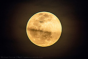 A commercial jet flies past the full moon off the coast of Jupiter, Florida, USA
