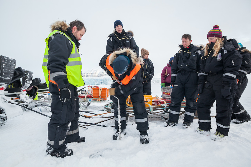Glaciologist Nick Hulton (left) and UNIS students watch their guide drill into the sea ice in Templefjorden, Svalbard to measure its thickness.