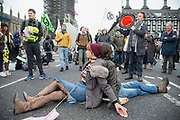 Two protesters sit on Westminster Bridge attached together by a D- lock on 7th October, 2019 in London, Untited Kingdom. Extinction Rebellion plan to occupy 12 sites situated around key Government locations around Westminster for two weeks to protest against climate change.