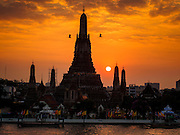 "19 DECEMBER 2013 - BANGKOK, THAILAND:  Sunset at Wat Arun. Wat Arun Ratchawararam Ratchawaramahawihan or Wat Arun (""Temple of Dawn""), a Buddhist temple (wat) in Bangkok Yai district of Bangkok, on the Thonburi side of the Chao Phraya River. The temple derives its name from the Hindu god Aruna, often personified as the radiations of the rising sun. Wat Arun is among the best known of Thailand's landmarks and the first light of the morning reflects off the surface of the temple with pearly iridescence. Although the temple had existed since at least the seventeenth century, its distinctive Khmer style prang (spires) were built in the early nineteenth century during the reign of King Rama II.        PHOTO BY JACK KURTZ"