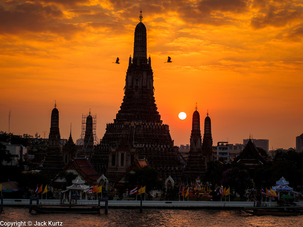 """19 DECEMBER 2013 - BANGKOK, THAILAND:  Sunset at Wat Arun. Wat Arun Ratchawararam Ratchawaramahawihan or Wat Arun (""""Temple of Dawn""""), a Buddhist temple (wat) in Bangkok Yai district of Bangkok, on the Thonburi side of the Chao Phraya River. The temple derives its name from the Hindu god Aruna, often personified as the radiations of the rising sun. Wat Arun is among the best known of Thailand's landmarks and the first light of the morning reflects off the surface of the temple with pearly iridescence. Although the temple had existed since at least the seventeenth century, its distinctive Khmer style prang (spires) were built in the early nineteenth century during the reign of King Rama II.        PHOTO BY JACK KURTZ"""
