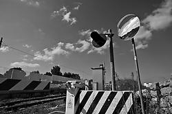il sole dell'alba riflette i suoi raggi nello specchio posto a margine dell'ennesimo passaggio a livello che taglia le strade del Salento. Reportage che analizza le situazioni che si incontrano durante un viaggio lungo le linee ferroviarie delle ferrovie Sud Est.
