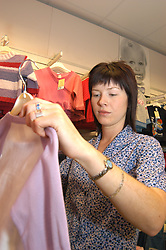 Female shop worker working in women's clothes shop; Merseyside; UK