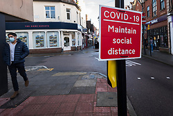 © Licensed to London News Pictures. 15/12/2020. RICKMANSWORTH, UK. A man wearing a facemask walks by a social distancing sign in the high street in Rickmansworth, Hertfordshire.  The historic town will be elevated to Tier 3 Covid Alert Level tomorrow, as part of the Three Rivers District Council area joining London and other areas of the South East as the number of coronavirus cases continues to rise.  Photo credit: Stephen Chung/LNP